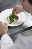 Male Chef Preparing Salad In Kitchen Stock Image