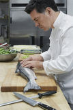 Male Chef Preparing Salmon In Kitchen. Side view of a middle aged male chef preparing salmon in kitchen Royalty Free Stock Images