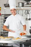 Male Chef Presenting Pasta Dish Royalty Free Stock Photos