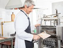 Male Chef Putting Ravioli Pasta In Machine At Stock Photography