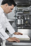 Male Chef Reading Recipe Book In Kitchen. Side view of a middle aged male chef reading recipe book in the kitchen Stock Image