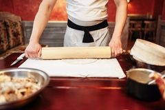 Male chef roll out the dough with a rolling pin. On wooden table. Homemade strudel cooking Royalty Free Stock Photos