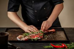 Male chef rubbing raw lamb shanks with greens and spices on stone tray on wooden table. Chef cooking appetizing shank of. Lamb. Training, master class, courses Stock Photo