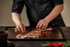 Male chef rubbing raw lamb shanks with greens and spices on stone tray on wooden table. Chef cooking appetizing shank of. Lamb. Training, master class, courses Royalty Free Stock Image