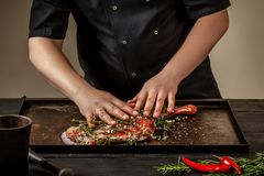 Male chef rubbing raw lamb shanks with greens and spices on stone tray on wooden table. Chef cooking appetizing shank of. Lamb. Training, master class, courses Stock Photos