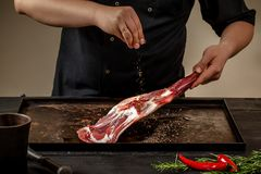 Male chef rubbing raw lamb shanks with salt and pepper on stone tray on wooden table. Chef cooking appetizing shank of. Lamb. Training, master class, courses Royalty Free Stock Photos