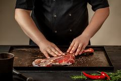Male chef rubbing raw lamb shanks with salt and pepper on stone tray on wooden table. Chef cooking appetizing shank of. Lamb. Training, master class, courses Royalty Free Stock Photography