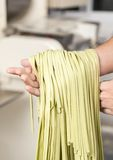 Male Chef's Hand Holding Green Spaghetti Pasta Stock Photography