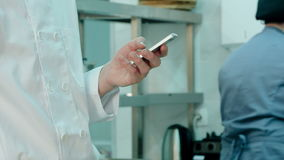 Male chef`s hands holding mobile phone in the restaurant kitchen stock video footage