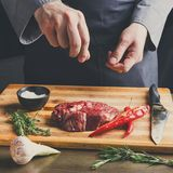 Chef seasoning rib eye steak on wooden board at restaurant kitch Stock Image