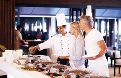 Male chef serving food to happy mature couple Royalty Free Stock Photos