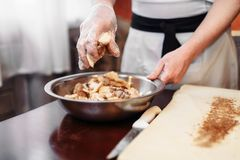 Male chef sprinkle the dough with cinnamon. Apple strudel cooking. Homemade sweet dessert, tasty pie preparation process Stock Image