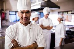 Male chef standing with arms crossed while coworker interacting with each other in kitchen. At hotel royalty free stock photos