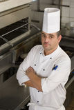 Male chef standing in commercial kitchen, arms folded, portrait, elevated view Stock Photos