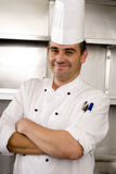Male chef standing in commercial kitchen, arms folded, smiling, portrait Royalty Free Stock Image