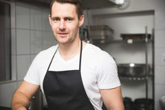 Male chef standing in kitchen. Front portrait of male chef standing in kitchen royalty free stock photo