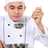 Male chef taste his cooking. Professional male chef taste his cooking isolated over white background Royalty Free Stock Photo