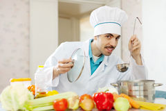 Male chef tasting soup with ladle Stock Image