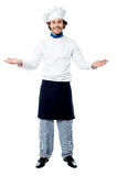 Male chef in uniform welcoming guests. Chef posing with his arms wide open, welcoming guests Royalty Free Stock Image