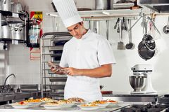 Male Chef Using Digital Tablet In Kitchen. Young male chef using digital tablet with pasta dishes at kitchen counter Stock Image
