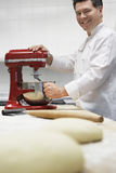 Male Chef Using Dough Mixer In Kitchen Stock Photo