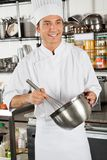 Male Chef Whisking Egg In Kitchen Stock Photo