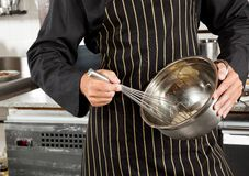 Male Chef Whisking Egg In Kitchen Royalty Free Stock Photography