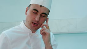 Male chef in white uniform talking on the phone while cooking stock footage