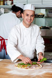Male chefs actively working in kitchen Stock Images