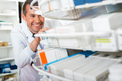 Male Chemist Counting Stock In Pharmacy Stock Photo