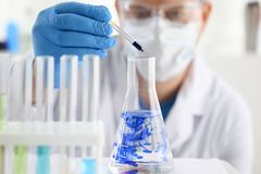 A male chemist holds test tube of glass. In his hand overflows a liquid solution of potassium permanganate conducts an analysis of water samples versions of stock photography