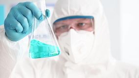 Male chemist lold test tube in hand. Mixing blue liquid in chemistry lab stock footage