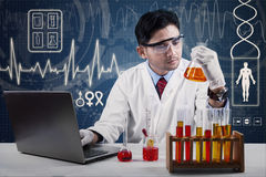 Male chemist looking at chemical glassware Royalty Free Stock Photography
