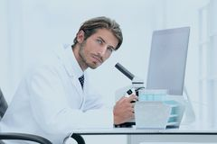 Male Chemist Scientific Reseacher using Microscope in Laboratory. E view of a male scientific researcher using microscope in the laboratory Royalty Free Stock Image