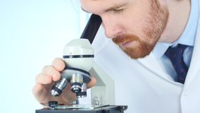 Male Chemist Scientific Reseacher using Microscope in Laboratory. 4k , high quality Stock Photos