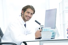 Male Chemist Scientific Reseacher using Microscope in Laboratory. Side view of a male scientific researcher using microscope in the laboratory Royalty Free Stock Photo