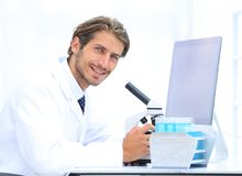 Male Chemist Scientific Reseacher using Microscope in Laboratory. Side view of a male scientific researcher using microscope in the laboratory Royalty Free Stock Image