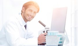Male Chemist Scientific Reseacher using Microscope in Laboratory. Side view of a male scientific researcher using microscope in the laboratory Royalty Free Stock Photos