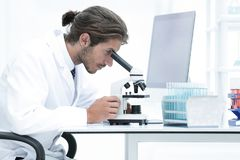 Male Chemist Scientific Reseacher using Microscope in Laboratory. Side view of a male scientific researcher using microscope in the laboratory Stock Photos