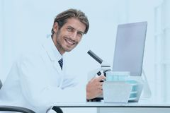 Male Chemist Scientific Reseacher using Microscope in Laboratory. Side view of a male scientific researcher using microscope in the laboratory Royalty Free Stock Photography