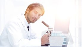 Male Chemist Scientific Reseacher using Microscope in Laboratory. Side view of a male scientific researcher using microscope in the laboratory Stock Image