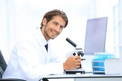 Male Chemist Scientific Reseacher using Microscope in Laboratory. Side view of a male scientific researcher using microscope in the laboratory Stock Images