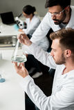 Male chemists in lab coats examining reagent in flask. Young male chemists in lab coats examining reagent in flask Royalty Free Stock Photo