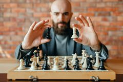 Male chess player holds white and black figures royalty free stock image