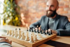 Male chess players, focus on board with figures. Male chess players begin playing, focus on board with figures. Two chessplayers begin the intellectual stock photo