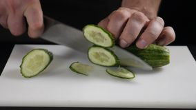 Male chief cook chopping vegetables, Slicing cucumber on white board. Close up. Man on kitchen cooking natural and. Healthy meal. Seasonal vegetables stock video