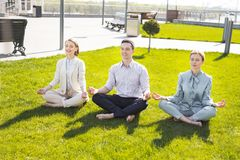 Male chief executive joining his female colleagues on yoga session outside. Yoga session. Tired stressed chief executive joining his female colleagues on royalty free stock image