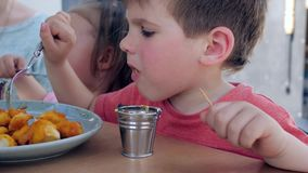 Male child eats fork with fried chicken nuggets with sauce, Boy and girl are having an appetizing dinner in restaurant, stock video footage