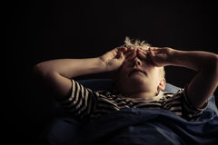 Male child rubbing eyes while laying in bed Stock Photo