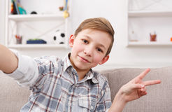 Male child taking selfie on phone at home. Happy child making selfie for social networks. Boy at home on sofa in living room Stock Photo